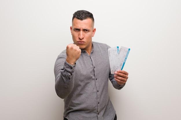 Jeune homme latin tenant un billet d'avion montrant le poing devant, expression fâchée