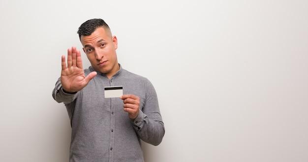 Jeune homme latin tenant une carte de crédit en mettant la main devant