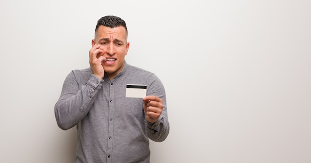 Jeune homme latin tenant une carte de crédit se ronger les ongles, nerveux et très inquiet