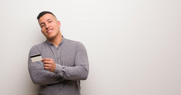 Jeune homme latin tenant une carte de crédit souriant confiant et croisant les bras, levant