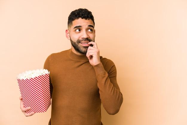 Jeune homme latin tenant un pop corn isolé pensée détendue sur quelque chose en regardant un espace de copie.