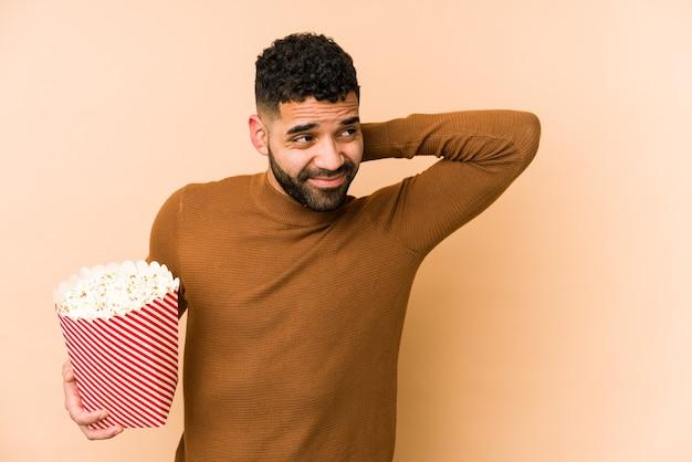 Jeune homme latin tenant un pop corn isolé toucher l'arrière de la tête, penser et faire un choix.