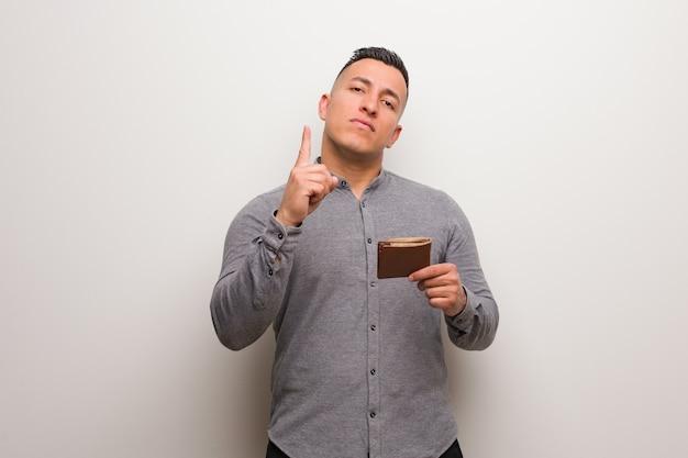 Jeune homme latin tenant un portefeuille montrant le numéro un