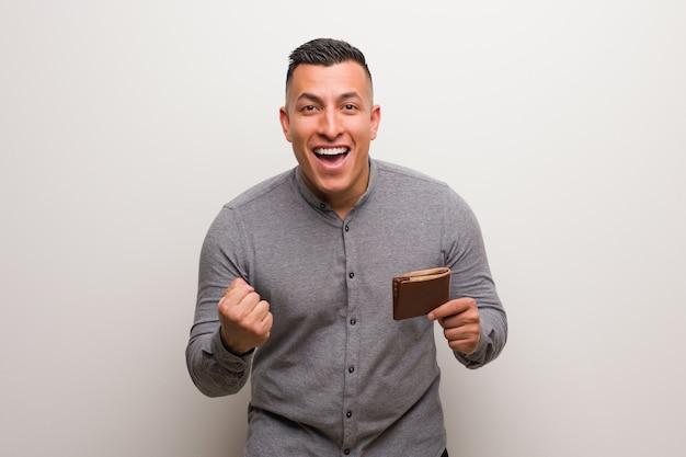 Jeune homme latin tenant un portefeuille surpris et choqué