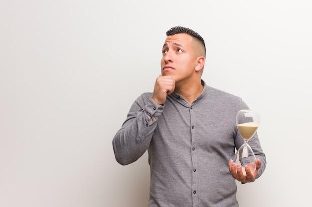 Jeune homme latin tenant un sablier doutant et confus