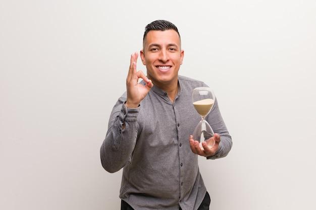 Jeune homme latin tenant un sablier joyeux et confiant faisant le geste ok