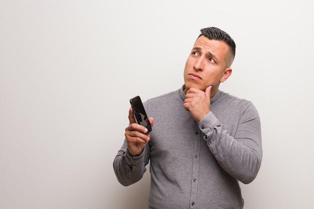 Jeune homme latin tenant un téléphone doutant et confus