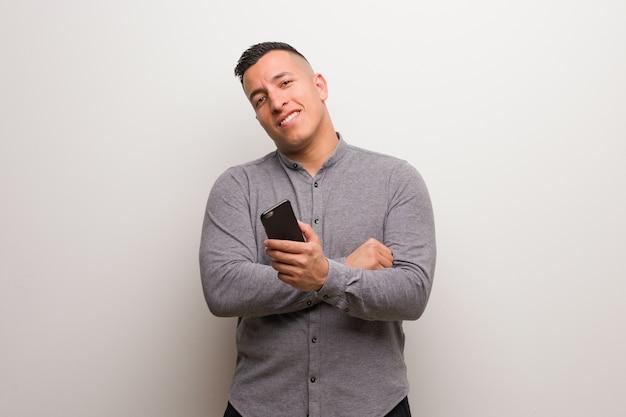 Jeune homme latin tenant un téléphone souriant confiant et croisant les bras, levant