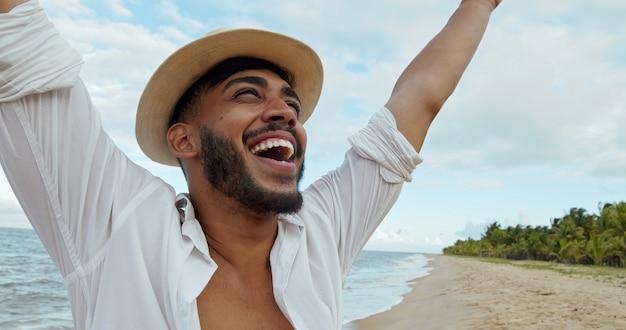 Jeune homme latino-américain sympathique sur la plage brésilienne