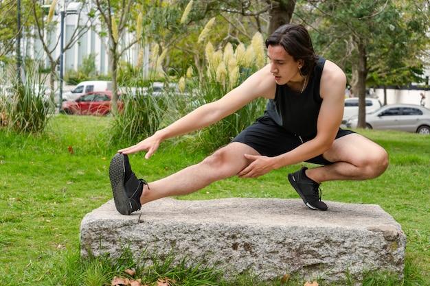 Jeune homme latino faisant des étirements musculaires après l'exercice. concept de vie saine.