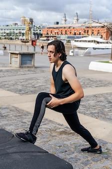 Jeune homme latino faisant des étirements musculaires avant l'exercice. concept de vie saine.