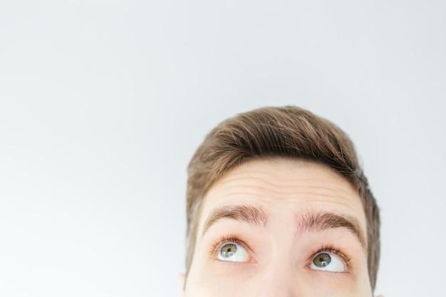 Jeune homme levant sur fond gris clair. tête d'homme