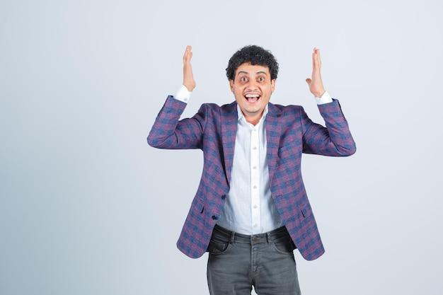 Jeune homme levant les mains en chemise, veste, pantalon et à la félicité, vue de face.