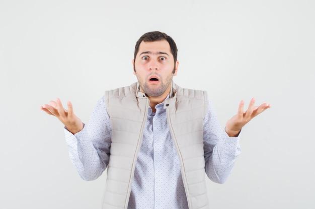 Jeune homme levant les mains de manière interrogative en chemise