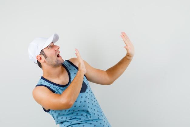 Jeune homme levant les mains pour se défendre en maillot bleu, casquette et à la peur. vue de face.