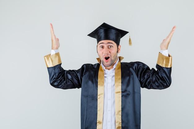 Jeune homme levant les mains en uniforme diplômé et à la vue de face, heureux