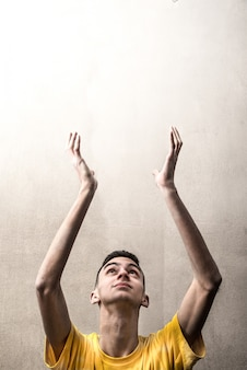 Jeune homme lève les bras