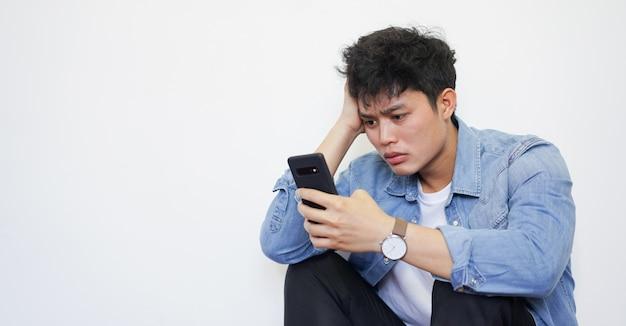 Jeune homme lisant des commentaires sur les réseaux sociaux