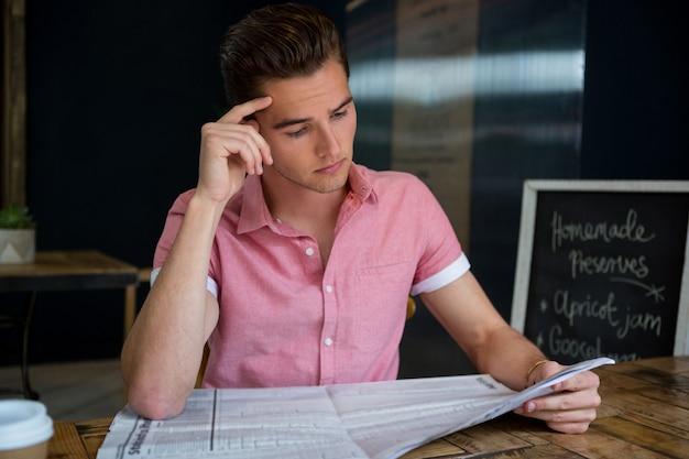 Jeune homme lisant le journal à table
