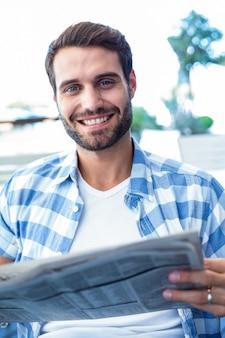 Jeune homme lisant les journaux