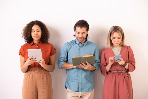 Jeune homme lisant un livre tout en surfant fille multiethnique à l'aide de gadgets modernes