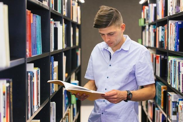 Jeune homme lisant un manuel
