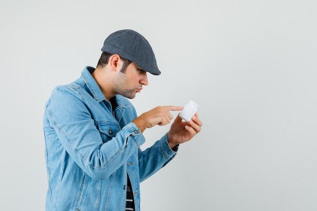 Jeune homme lisant le nom de pilules en veste, casquette et à la recherche concentrée. .