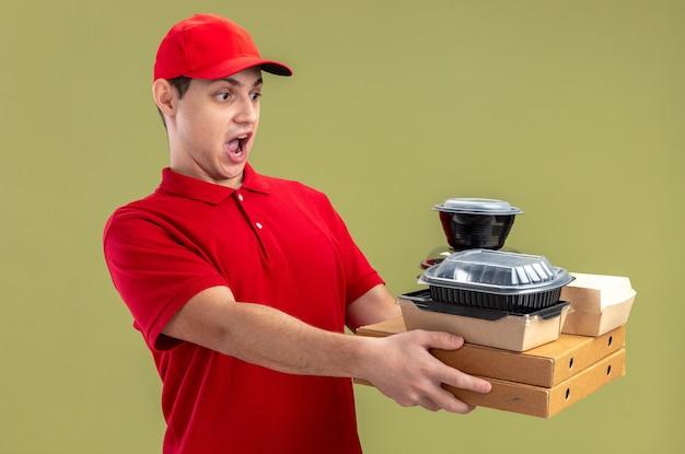 Jeune homme de livraison caucasien excité en chemise rouge tenant des contenants de nourriture sur des boîtes à pizza