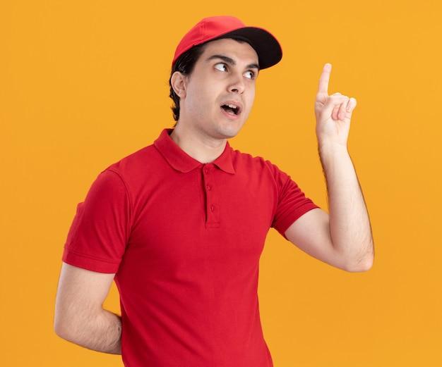 Jeune homme de livraison caucasien impressionné en uniforme bleu et casquette gardant la main derrière le dos pointant vers le haut en regardant le côté