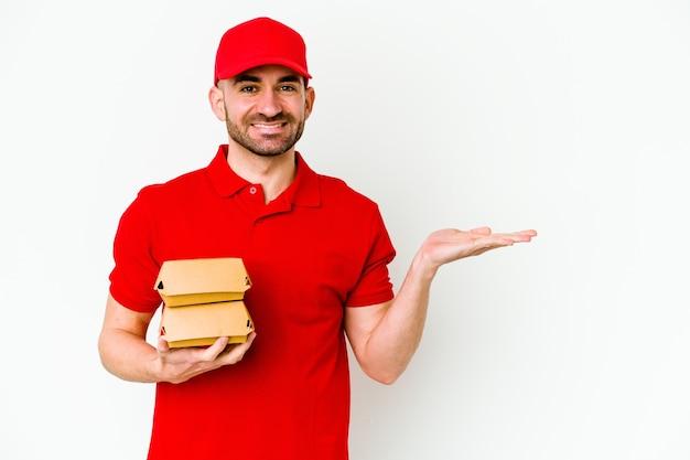 Jeune homme de livraison caucasien isolé sur un mur blanc montrant un espace de copie sur une paume et tenant une autre main sur la taille