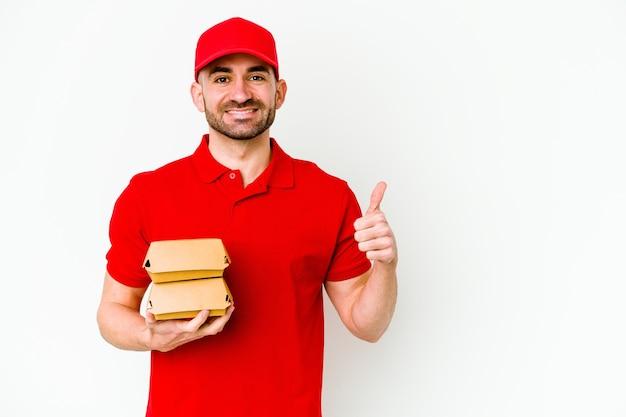 Jeune homme de livraison caucasien isolé sur un mur blanc souriant et levant le pouce vers le haut