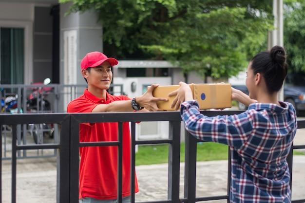 Jeune homme livrant le paquet au client à la maison. livraison