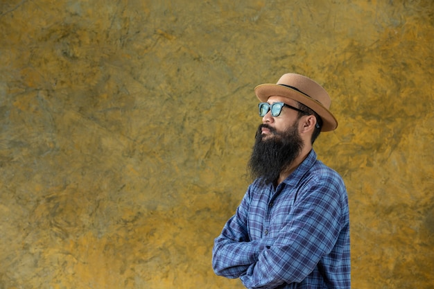 Jeune homme avec une longue barbe portant un chapeau et des lunettes