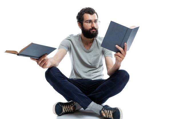 Un jeune homme avec des lunettes et une barbe est assis dans une pose de yoga et tient des livres dans ses mains. éducation et formation. isolé.