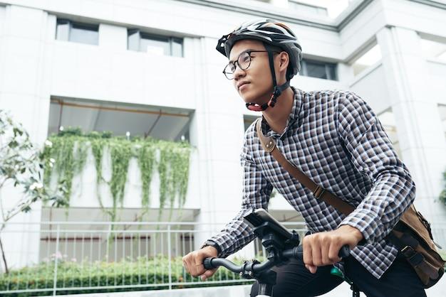 Jeune homme à lunettes et casque se dépêchant de travailler, il fait du vélo dans la rue