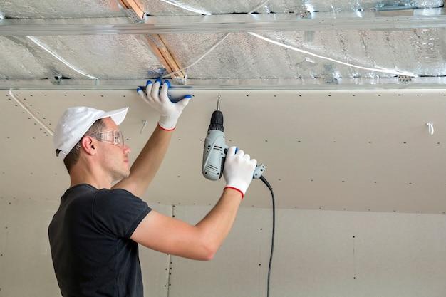 Jeune homme à lunettes fixant le plafond suspendu de cloisons sèches au cadre métallique à l'aide d'un tournevis électrique sur le plafond isolé avec du papier d'aluminium brillant. rénovation, construction, concept à faire soi-même.