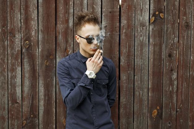Jeune homme à lunettes lance de la fumée et fume une cigarette près d'un mur en bois
