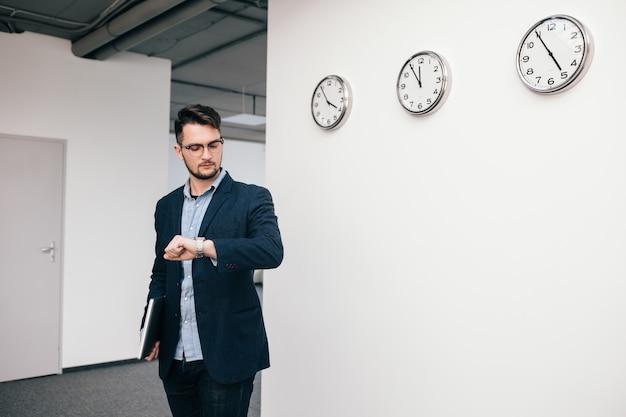 Jeune homme à lunettes marche au bureau. il porte une chemise bleue, une veste sombre, un jean et une barbe. il tient un ordinateur portable à la main. il regarde la montre.