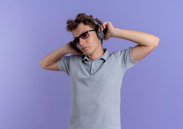Jeune homme à lunettes noires portant un polo gris avec des écouteurs en appréciant sa musique préférée debout sur un mur bleu