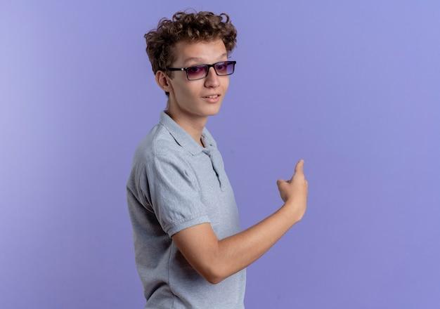 Jeune homme à lunettes noires portant un polo gris looking at camera smiling confiant pointant vers l'arrière sur bleu