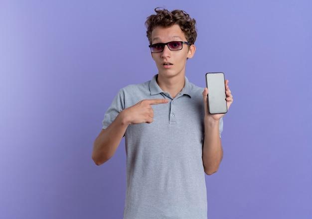 Jeune homme à lunettes noires portant un polo gris montrant smartphone pointant avec le doigt à être surpris debout sur le mur bleu