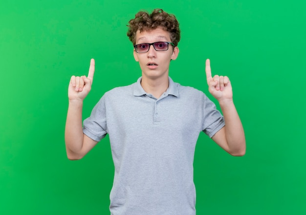 Jeune homme à lunettes noires portant un polo gris pointant avec les doigts idex d'être surpris debout sur le mur vert