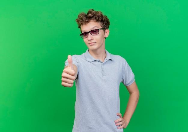 Jeune homme à lunettes noires portant un polo gris souriant hapy et positif montrant les pouces vers le haut debout sur le mur vert