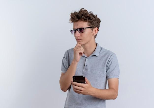 Jeune homme à lunettes noires portant un polo gris tenant le smartphone à côté avec la main sur le menton avec une expression pensive debout sur un mur blanc