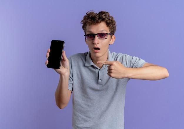 Jeune homme à lunettes noires portant un polo gris tenant le smartphone pointant avec l'index à être surpris debout sur le mur bleu