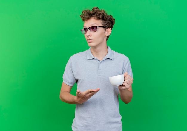 Jeune homme à lunettes noires portant un polo gris tenant une tasse de café présentant avec bras à côté avec une expression confiante sérieuse sur vert
