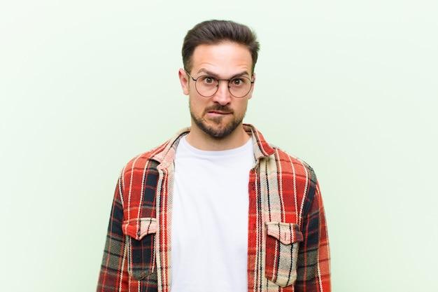 Un jeune homme avec des lunettes posant tout en se mordant la lèvre avec un geste nerveux