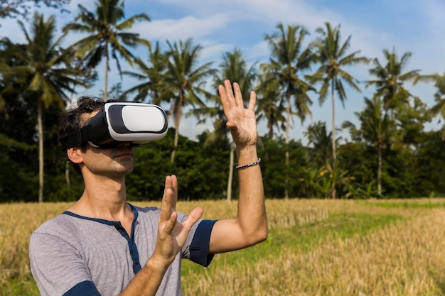 Jeune homme avec des lunettes de réalité virtuelle dans la rizière tropicale