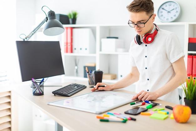Un jeune homme à lunettes se tient près d'un bureau d'ordinateur. un jeune homme dessine un marqueur sur un tableau magnétique. les écouteurs du mec pendent au cou.