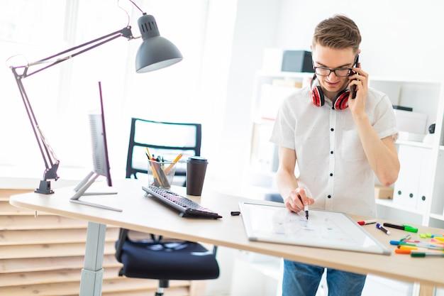 Un jeune homme à lunettes se tient près d'un bureau d'ordinateur et parle au téléphone. devant lui se trouvent un tableau magnétique et des balises. les écouteurs du mec pendent au cou.